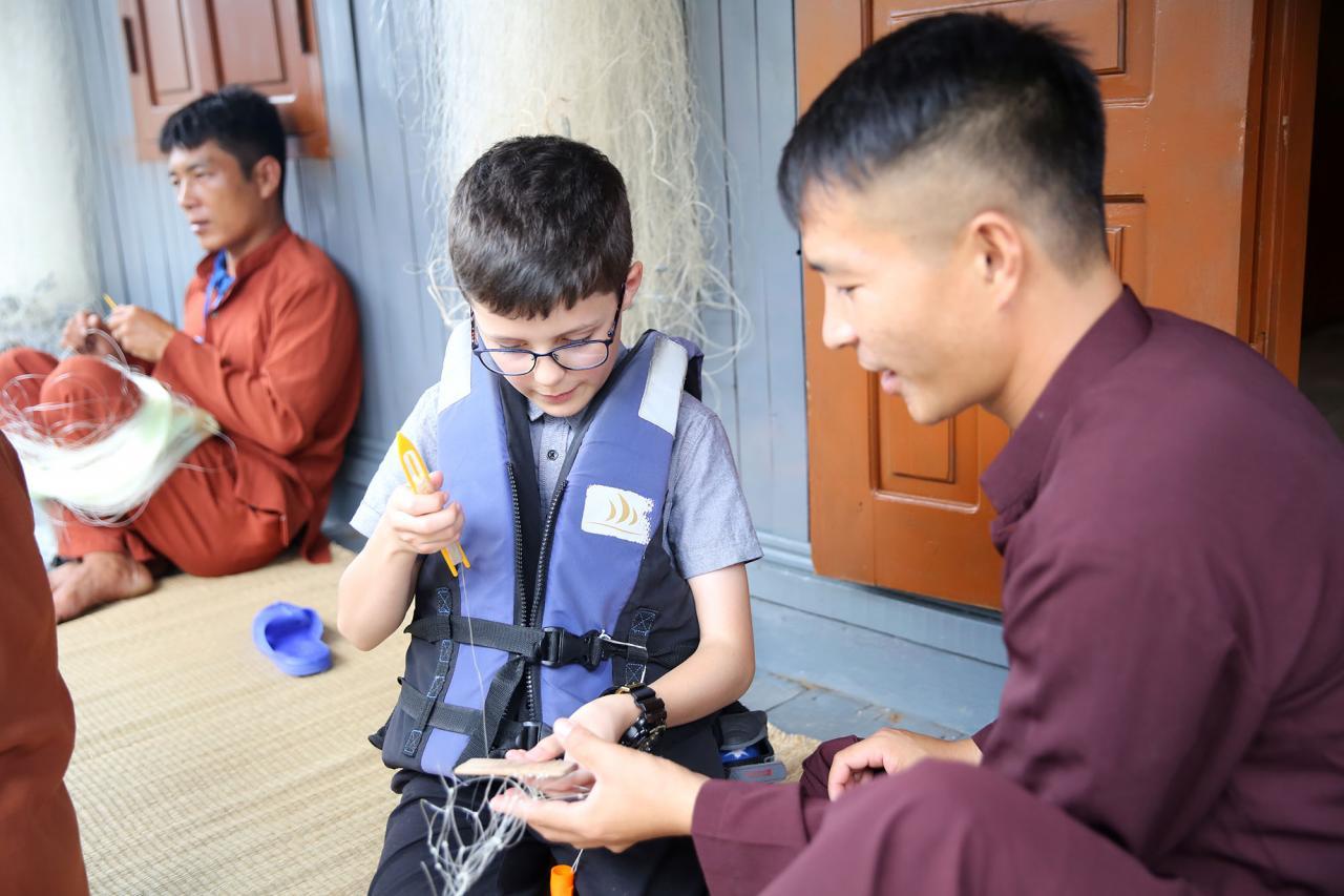 Em bé người nước ngoài thích thú khi được tận tay làm công việc truyền thống của dân chài vùng biển Hạ Long.
